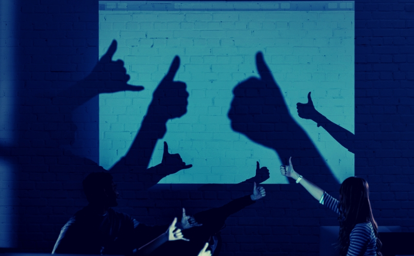 Group of friends giving thumbs up on projector screen