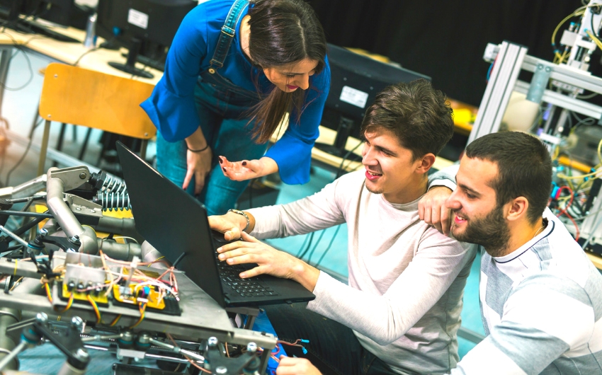 Three engineering students working on a laptop