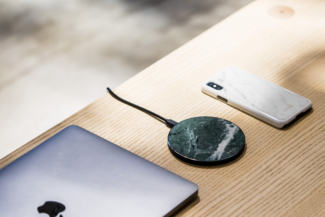 a wireless charger between a smart phone and a tablet